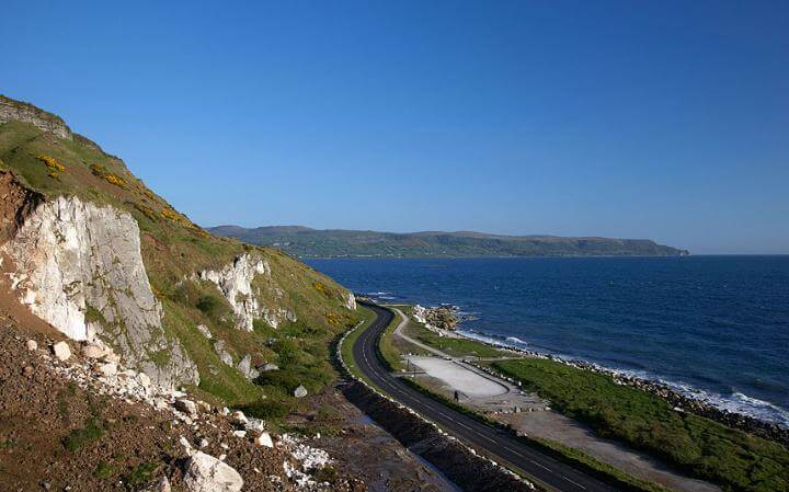 Coastal Northern Irish road leading through beautiful hills on sunny day