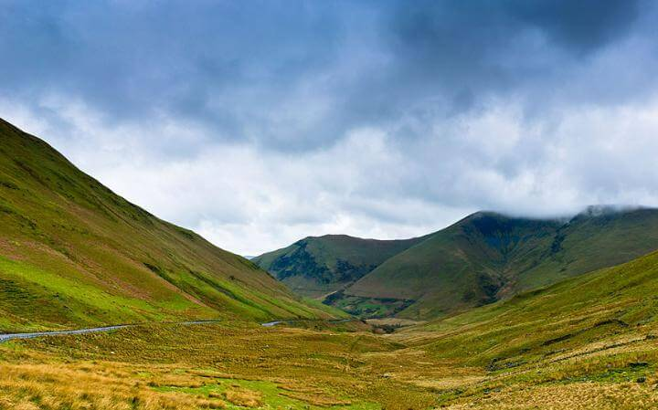 A470 Welsh road leading through valley surrounded by stunning green hills on overcast, cloudy day