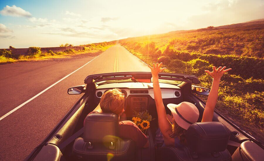 Happy couple in convertible car driving into the sunset on one of the UKs most scenic routes