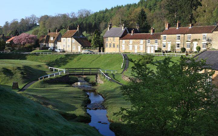pretty English village Hutton-Le-Hole with small river, footbridge and row of houses making this one of the UKs most scenic routes
