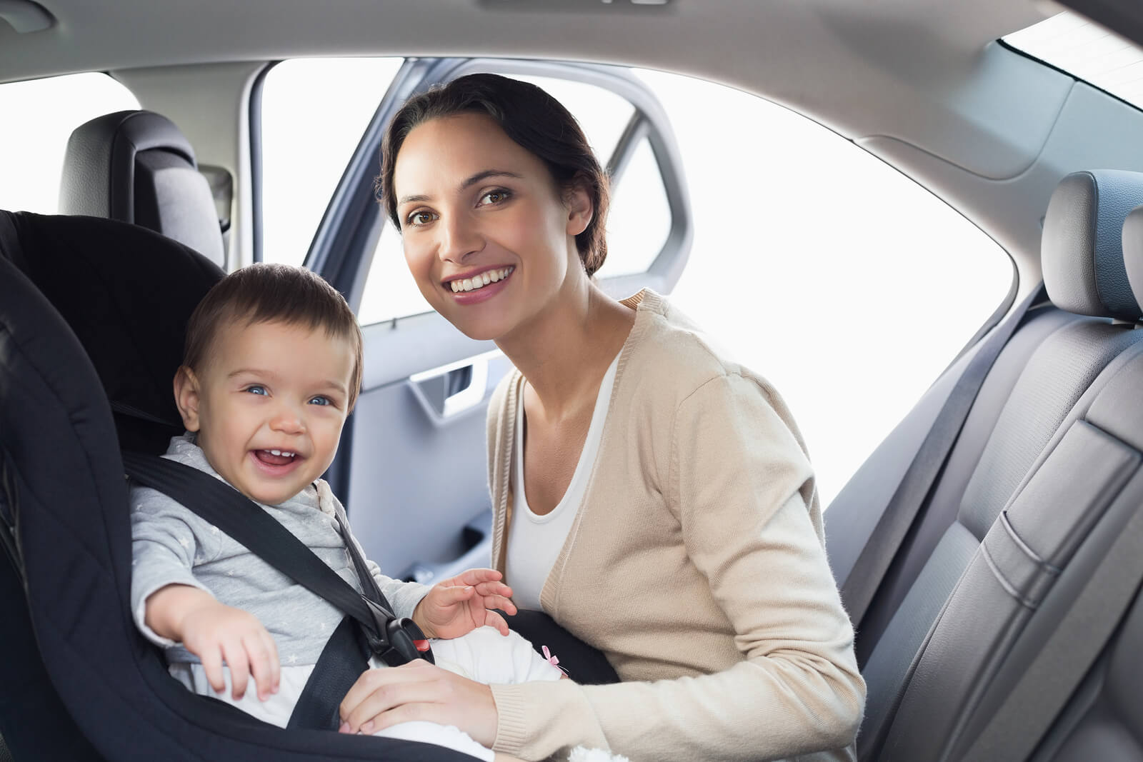 baby strapped into car seat with smiling parent about to begin a long car journey