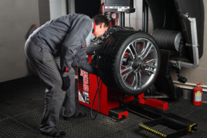 Mechanic conducting tire balancing in a workshop as part of a car service