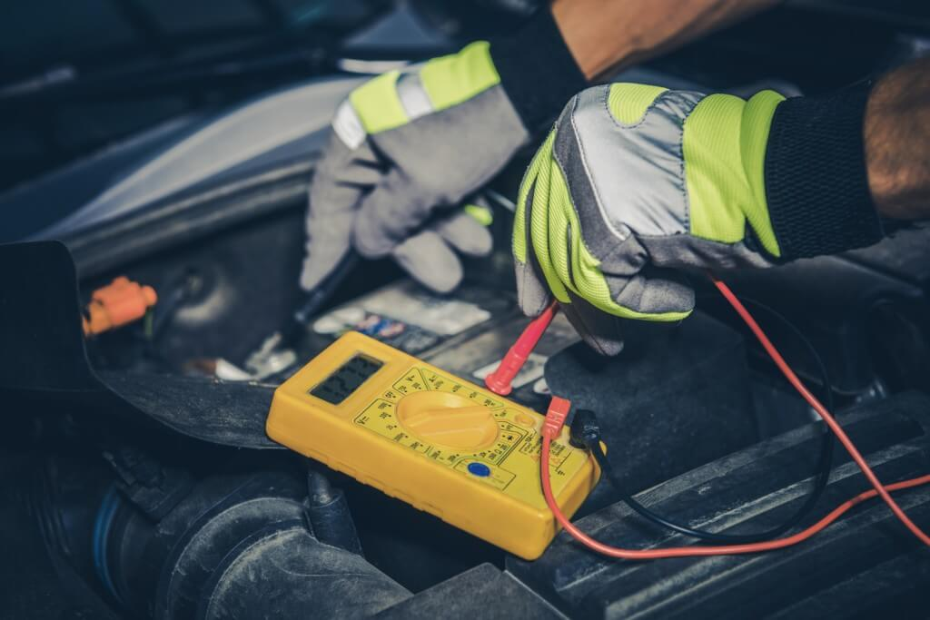 Mechanic in high vis gloves testing car battery with yellow machine