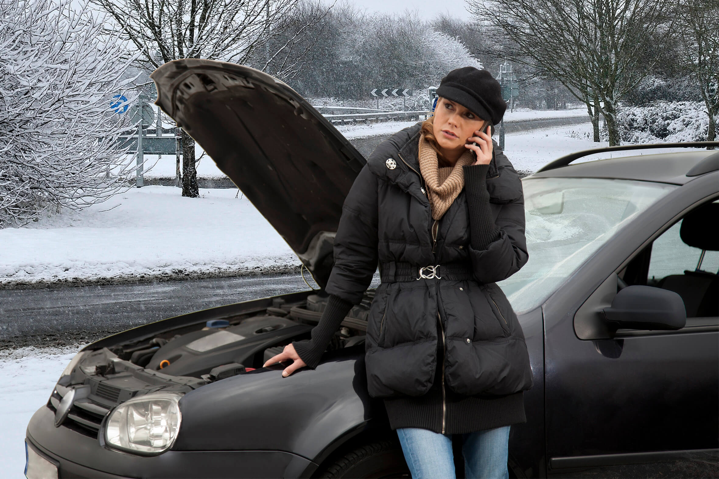 broken down black car with bonnet raised and concerned female driver on mobile phone, car battery issues