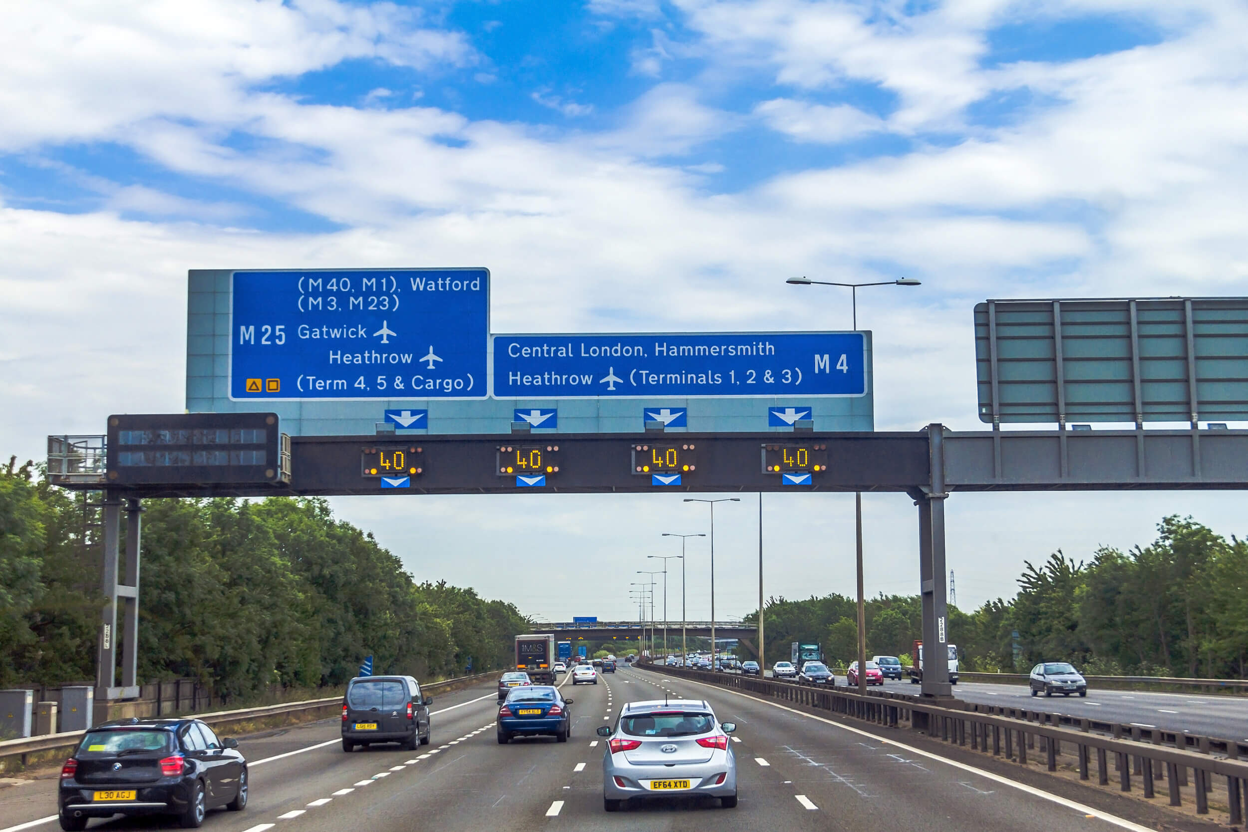 Motorway direction signs with cars avoiding speeding fines by driving below 70 mph