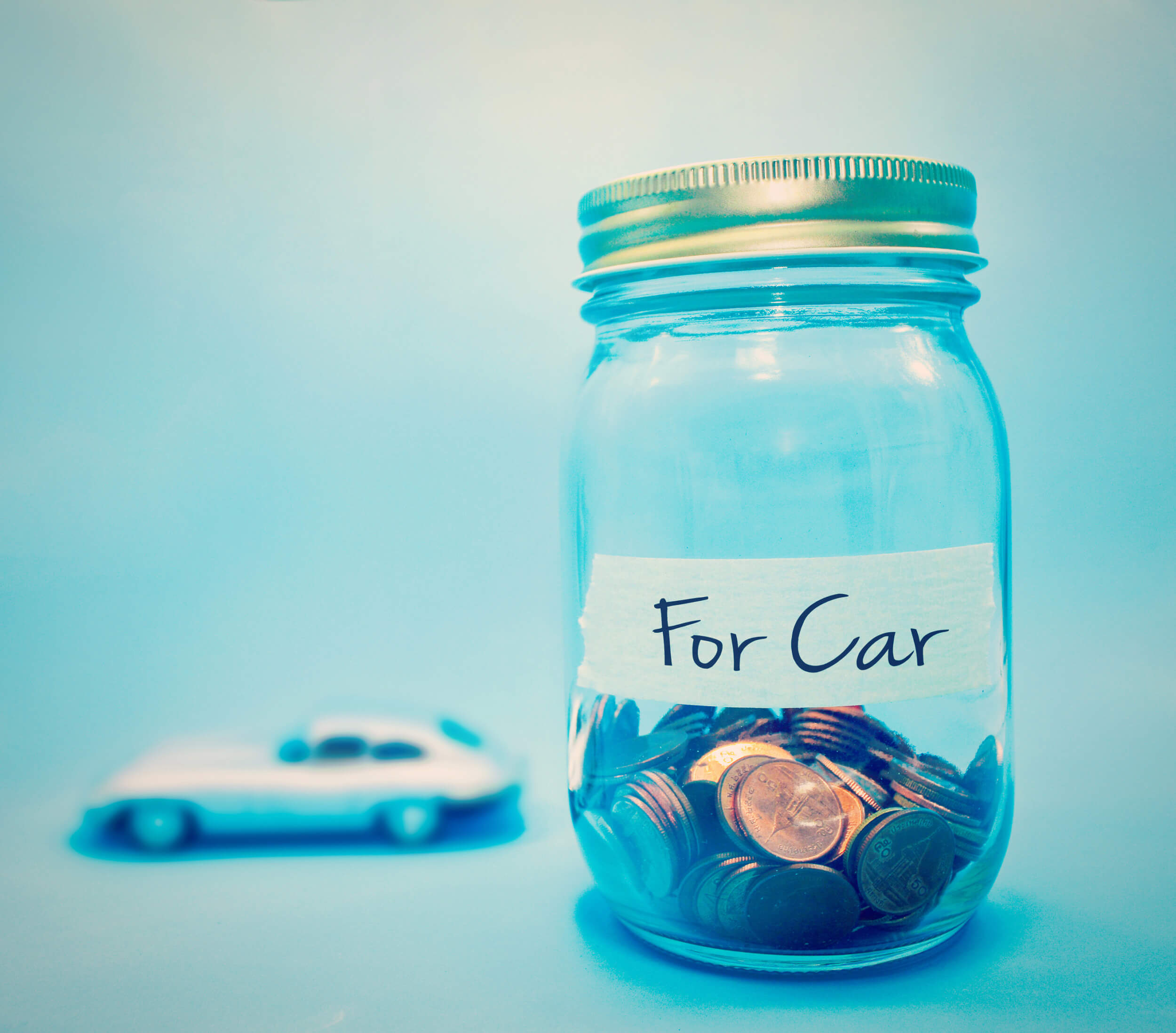 Toy car and large money saving jar to represent car running costs with light blue background