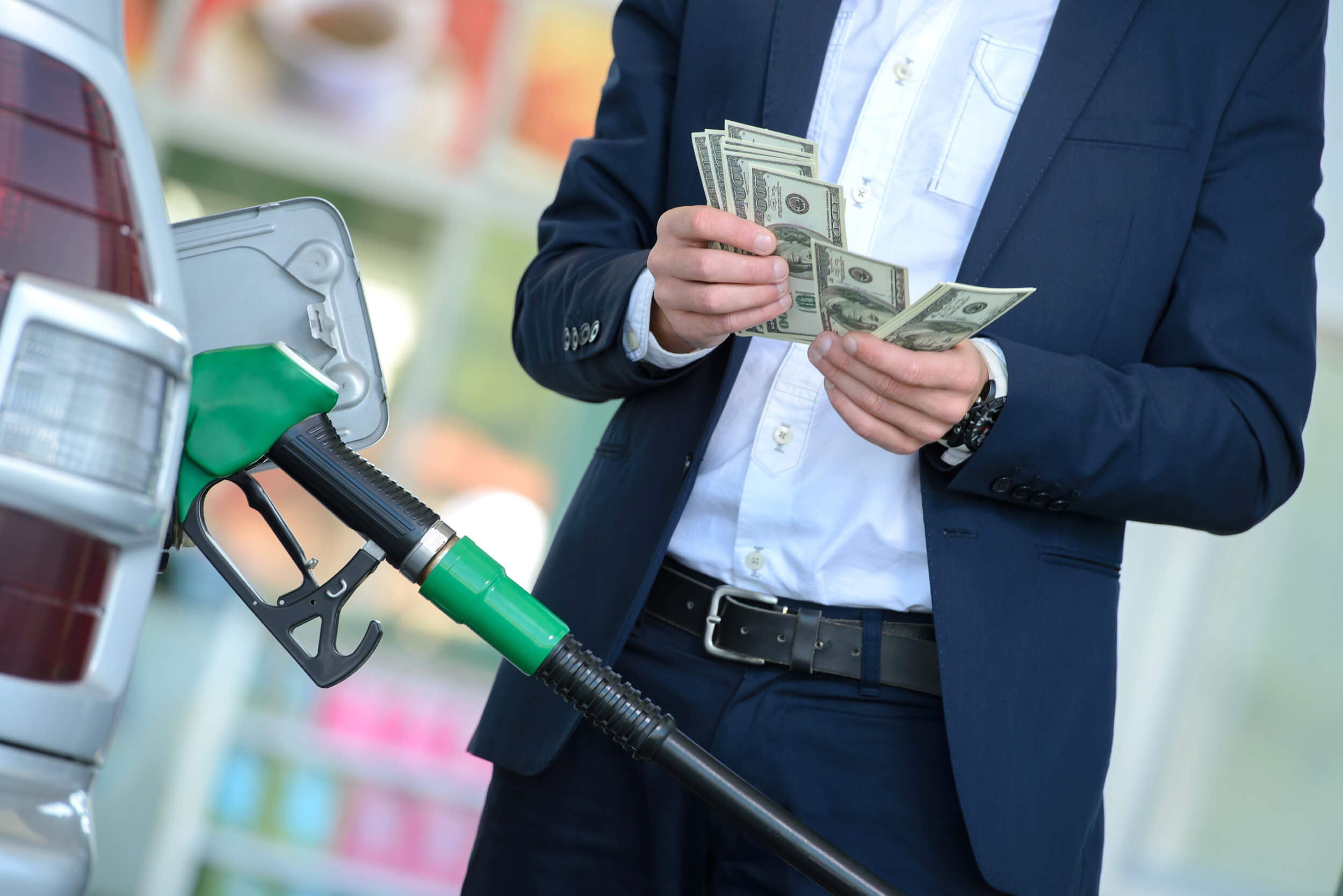 Person counting cash at a petrol station with the fuel pump filling the car