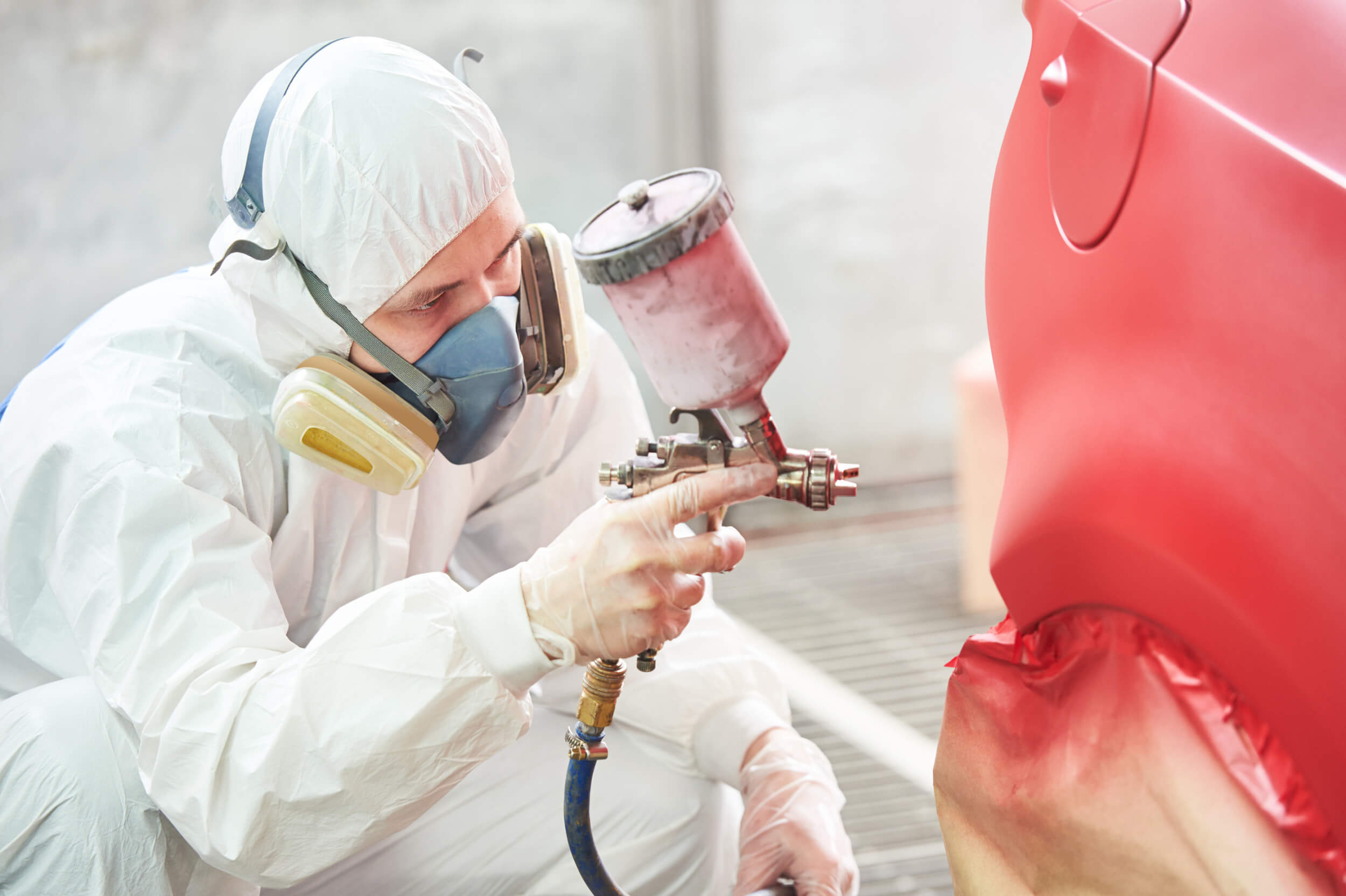 Technician in white protective suit spray painting car red to make it feel like new