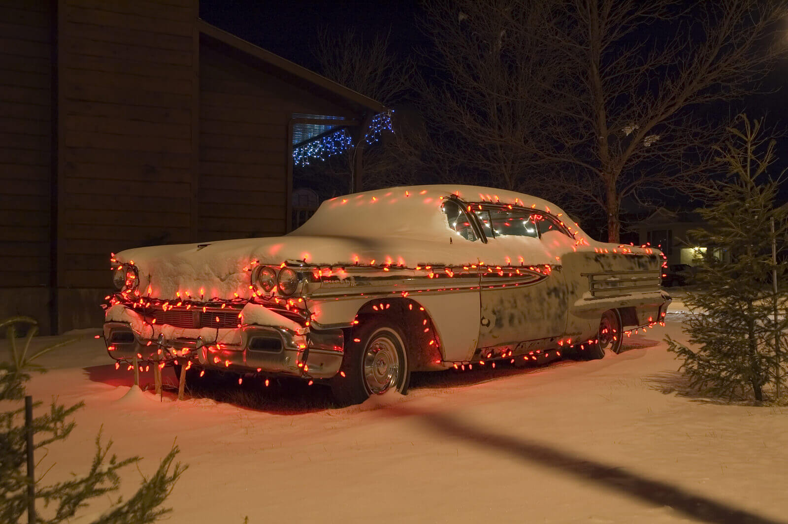Snow covered car decorated with red christmas lights