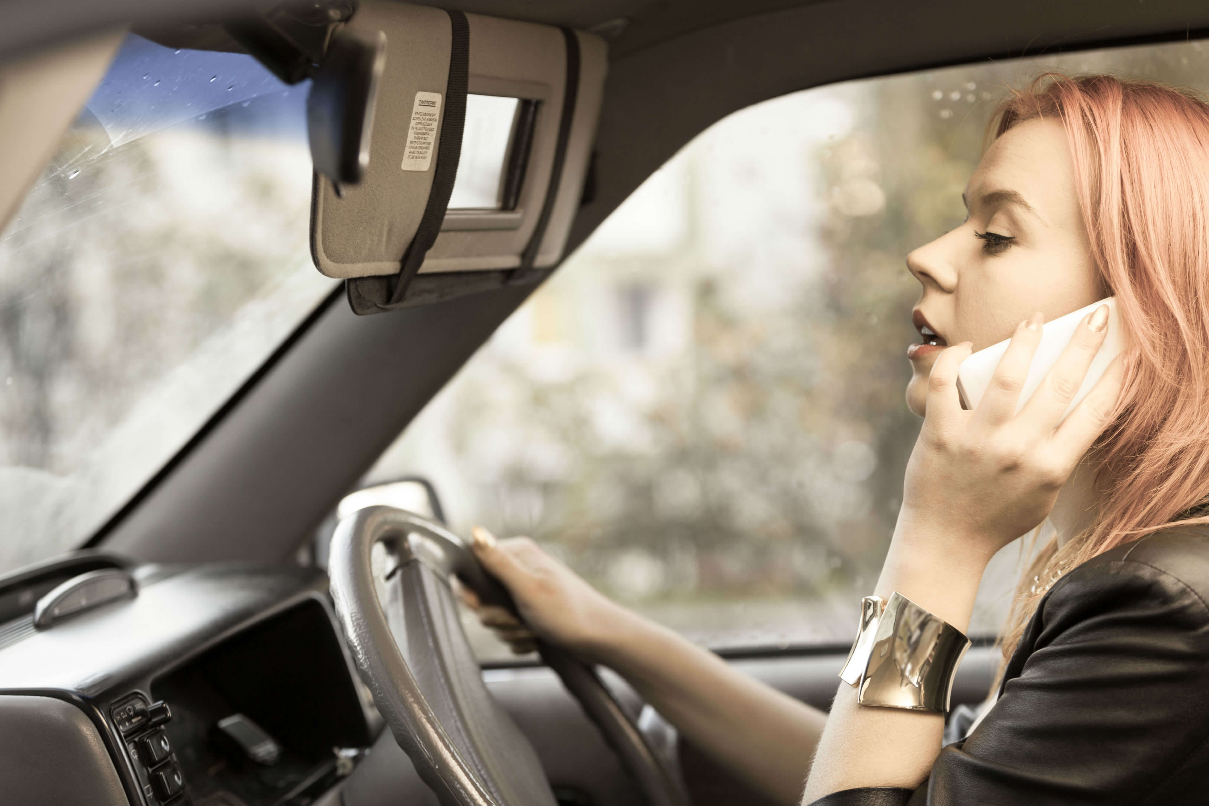female driver talking on mobile phone while driving her car and looking in the sunvisor mirror