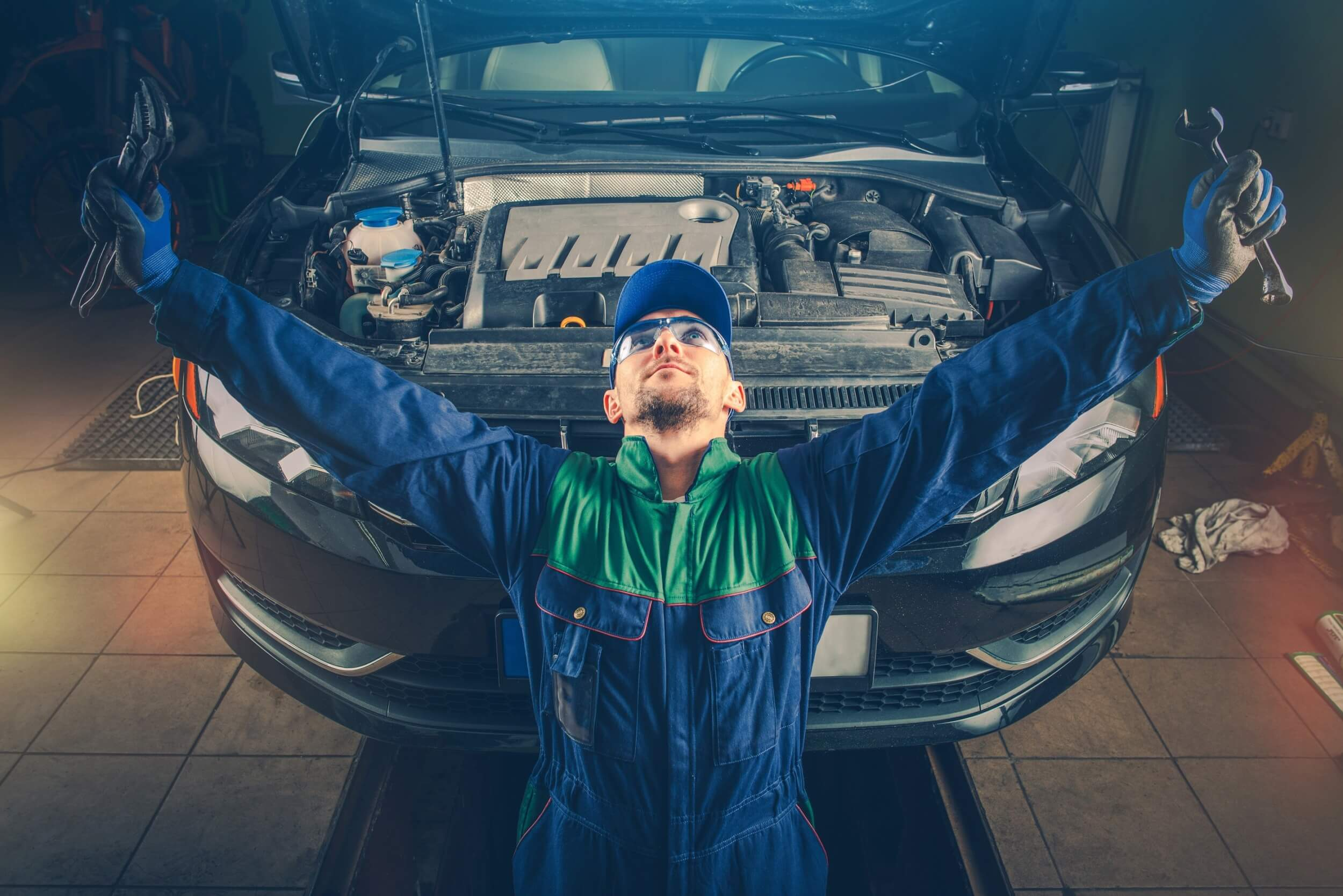 Car service mechanic raising arms in triumph after answering tricky question from a customer