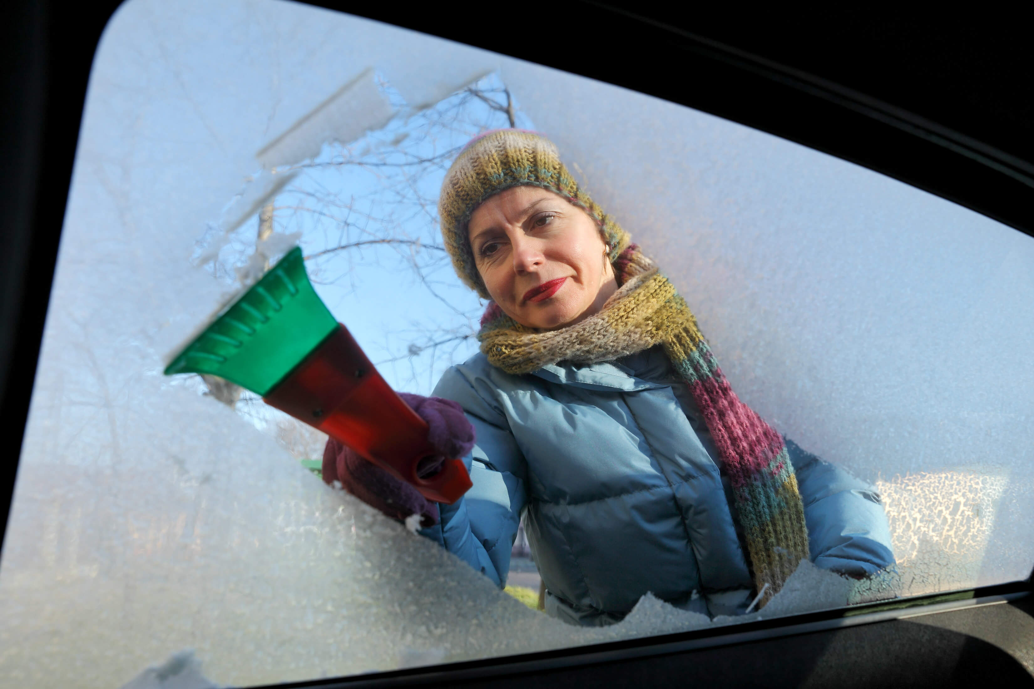 woman wrapped in thick coat, scarf and hat scraping windscreen with de-icer on cold, frosty winter morning