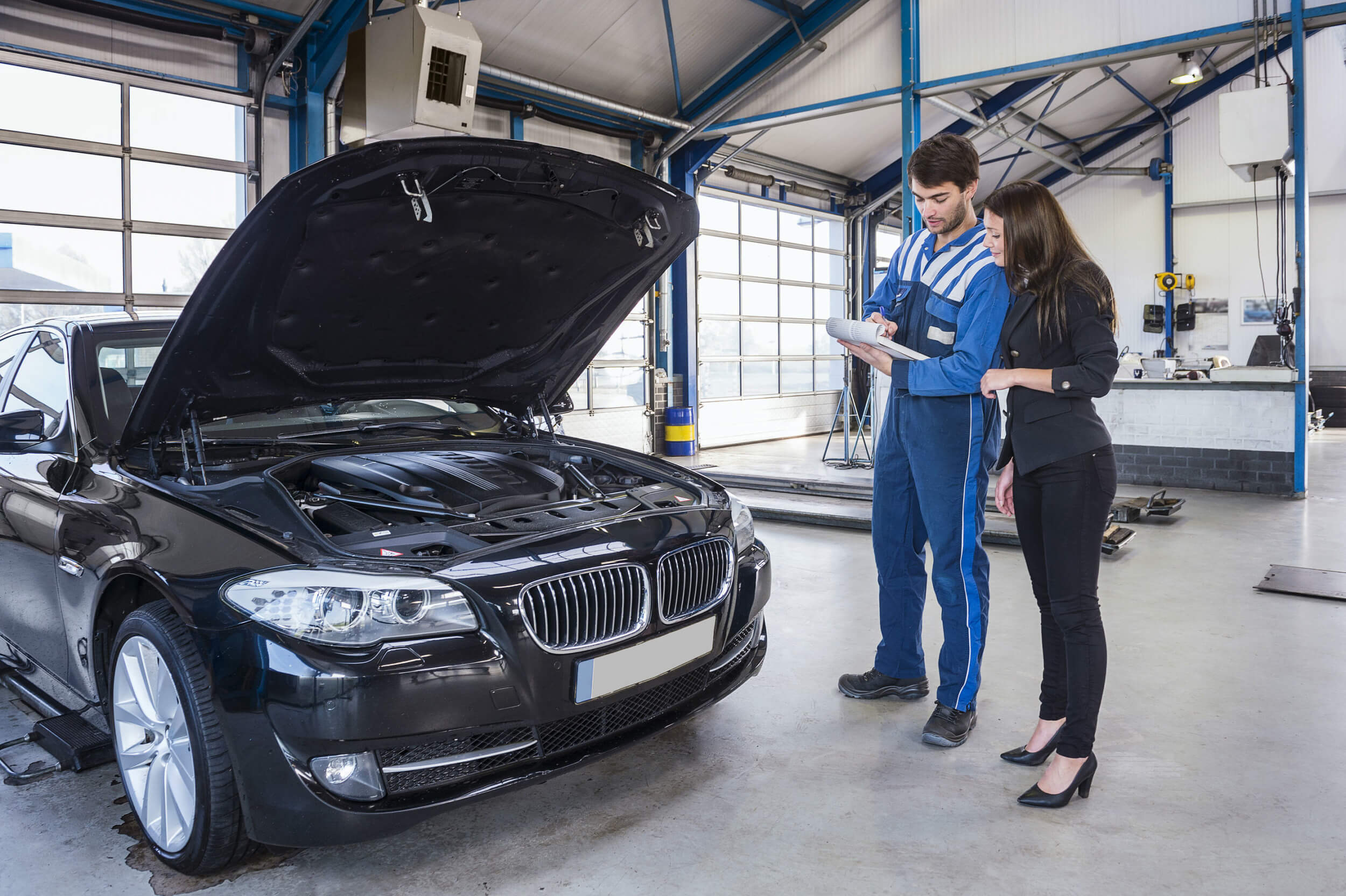 Mechanic explaining necessary repair work for the black BMW to the owner during a car service