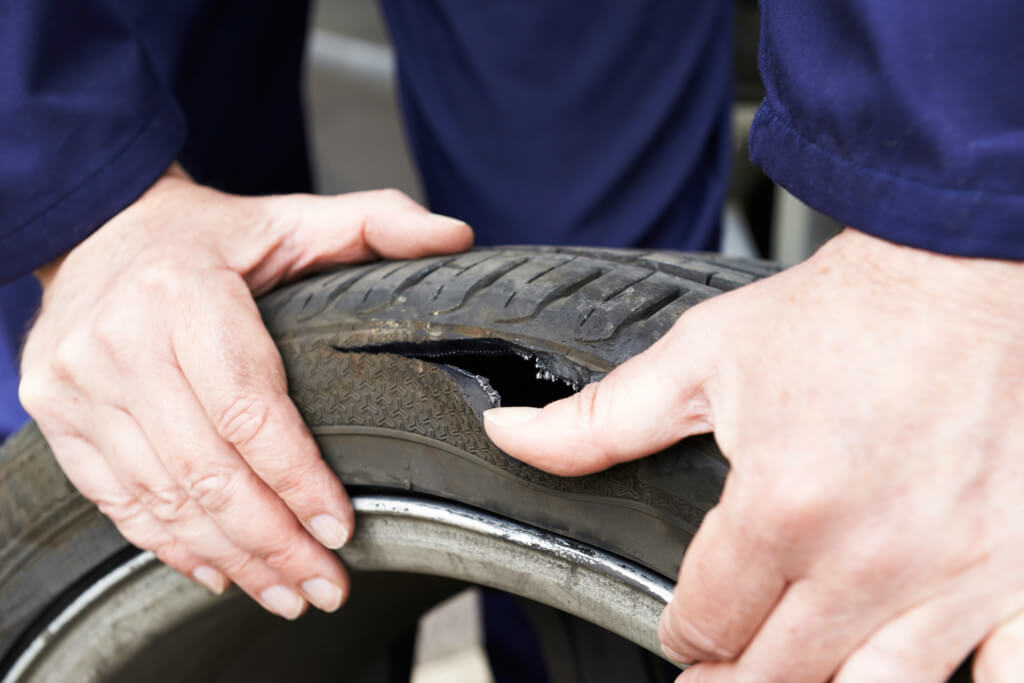 Incredibly damaged tyre caused by a pothole, split rubber and mechanic hands showing the gap