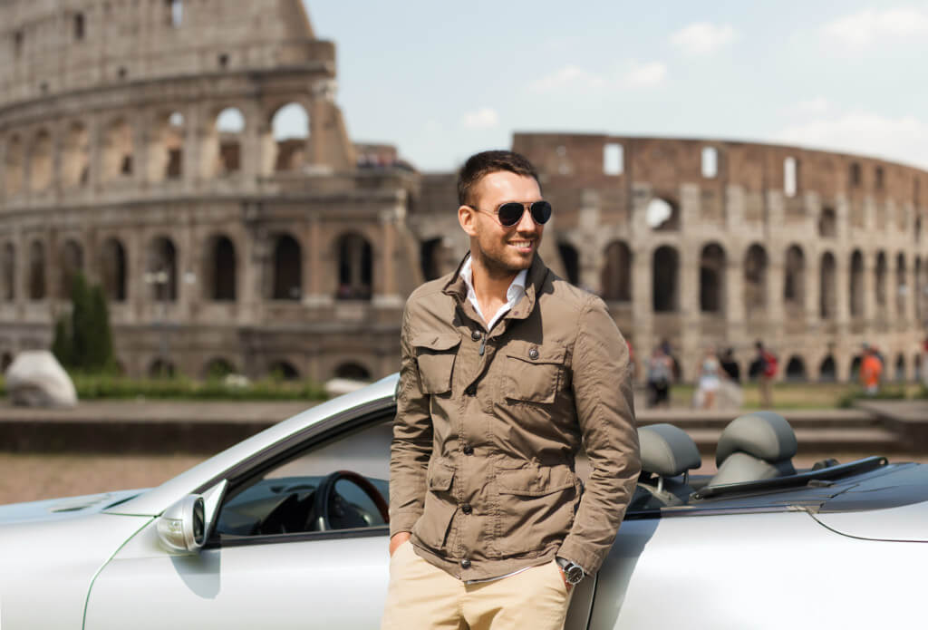 Happy driver in sunglasses leaning against silver car with the Colosseum in Rome in the background