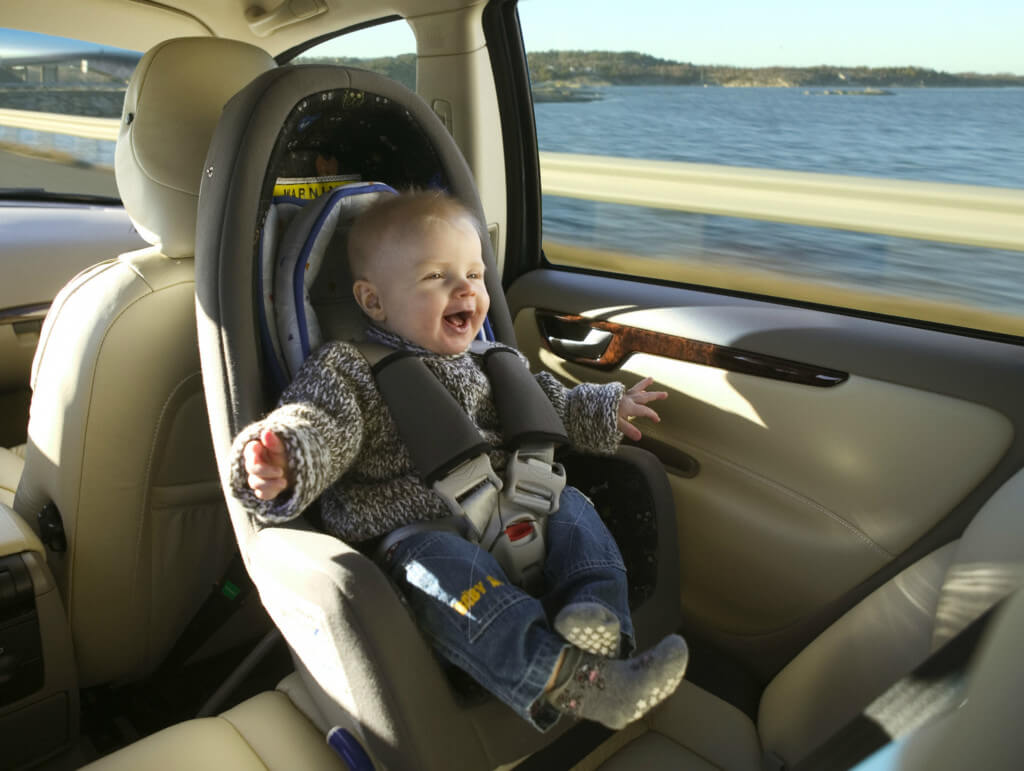 Smiling baby strapped into child seat travelling as a passenger along a seafront road