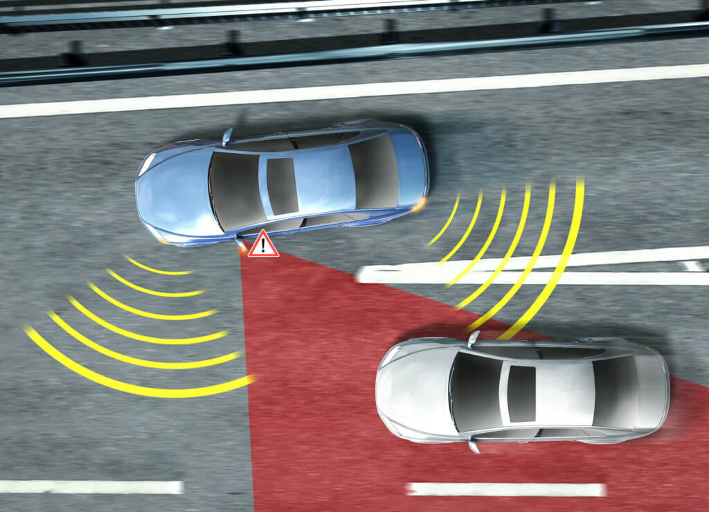 A representation of blind-spot monitoring safety feature - a blue car is joining a motorway and the technology recognises the silver car in the driver's blind spot and informs them to avoid an accident