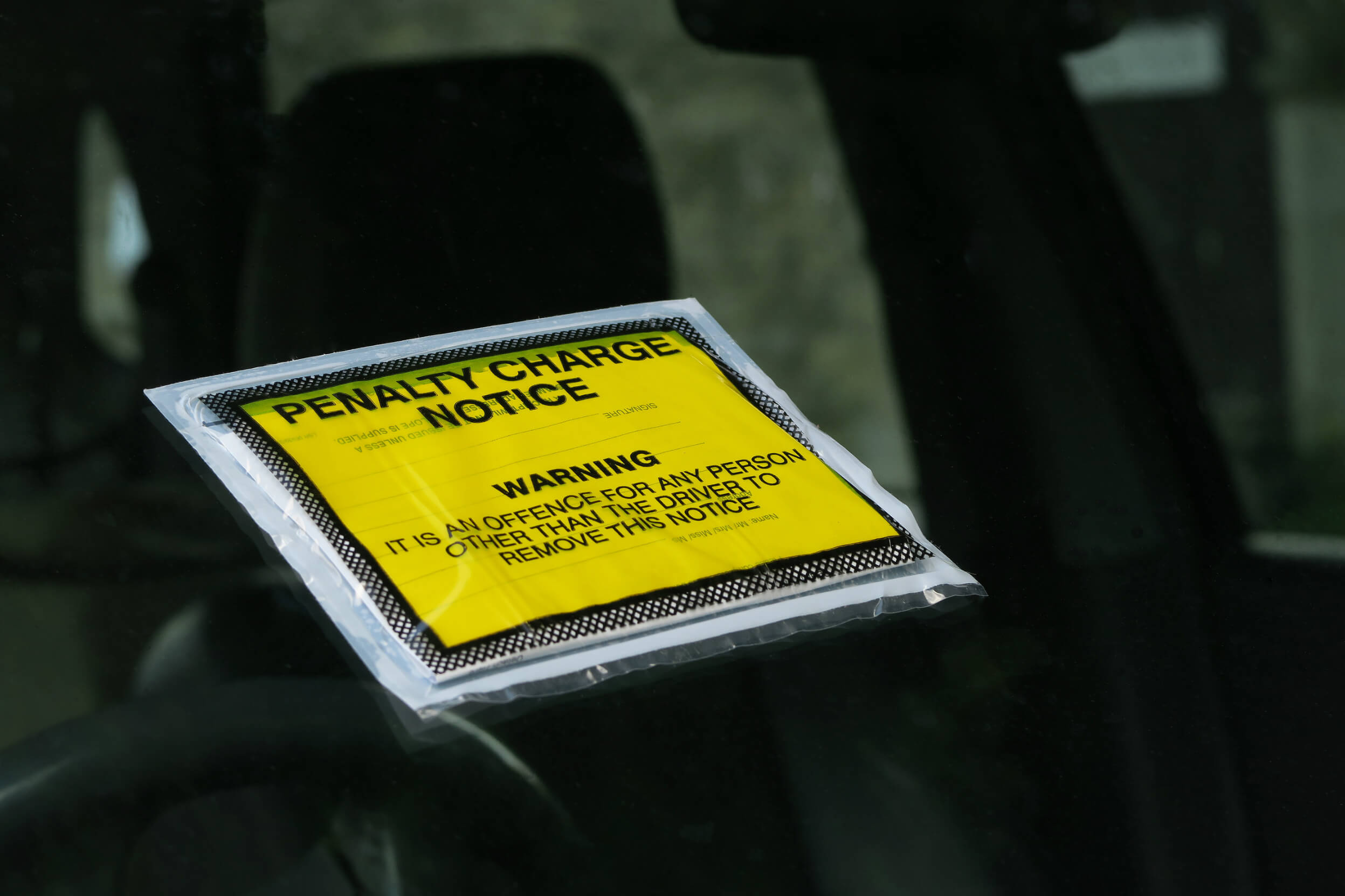 Yellow UK parking ticket stuck to car windscreen