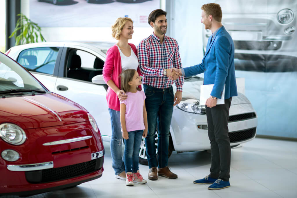 Smiling family shaking hands with car salesperson after securing deal on new car to help them beat car tax changes