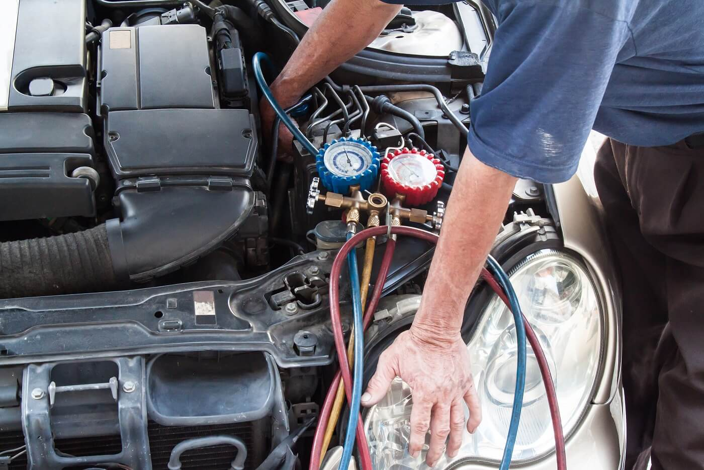 air con regas in progress, mechanic checking flow of refrigerant gas with specialist equipment