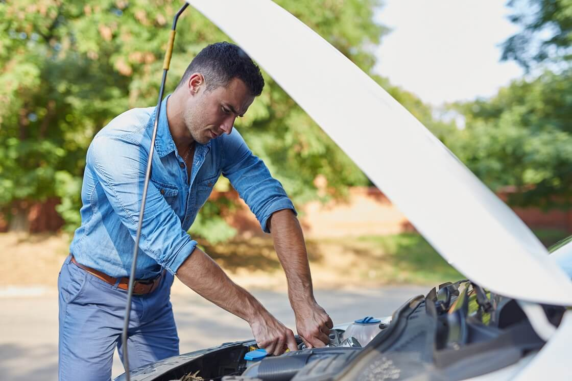 Driver conducting personal safety check by inspecting various engine parts under the bonnet