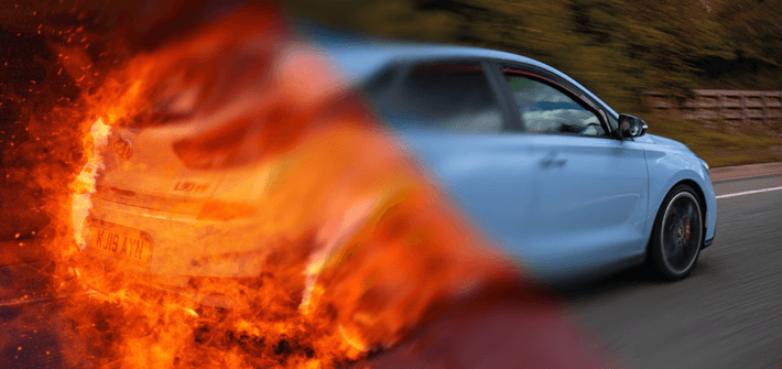 blue car half on fire driving down road representing broken air conditioning system and how an air con regas can make cars cool again