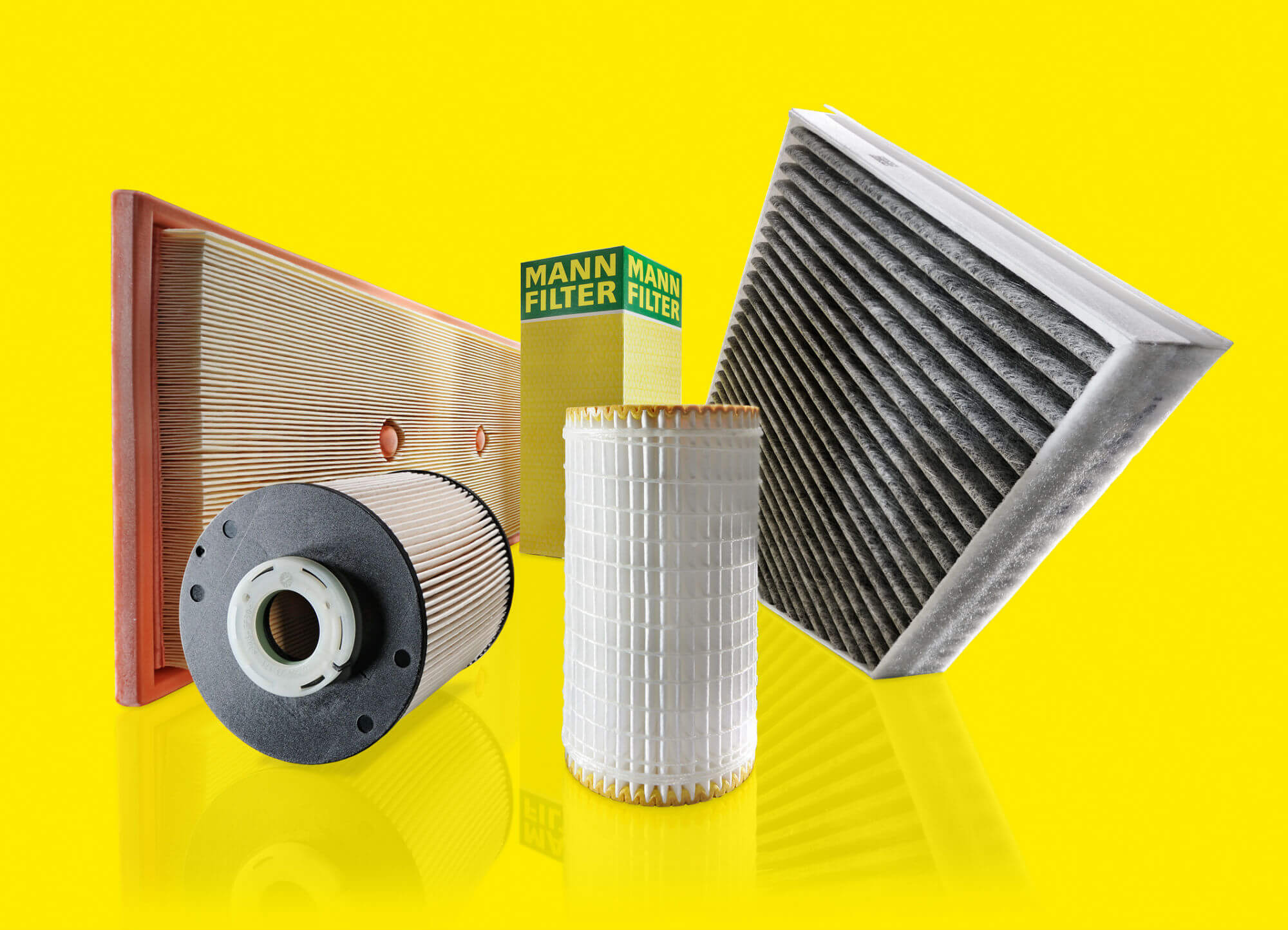 Different car cabin air filters arranged in front of a yellow background
