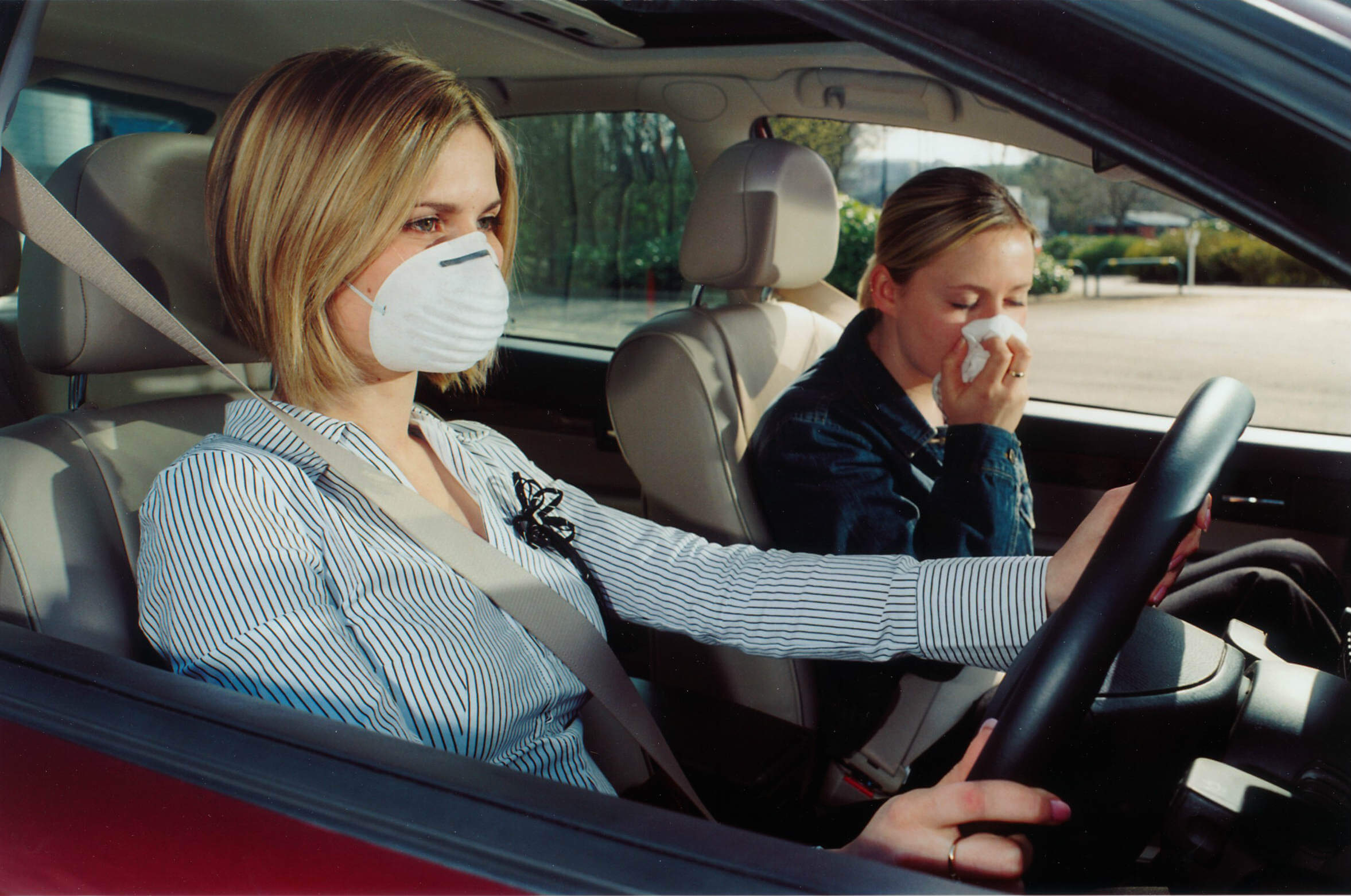 Driver and passenger wearing face masks to protect them from harmful bacteria in cabin air system due to lack of air filter change