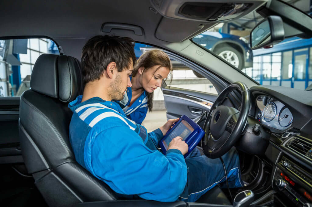 Male and female mechanic inspecting tablet while connected to car diagnostic port to find the problem