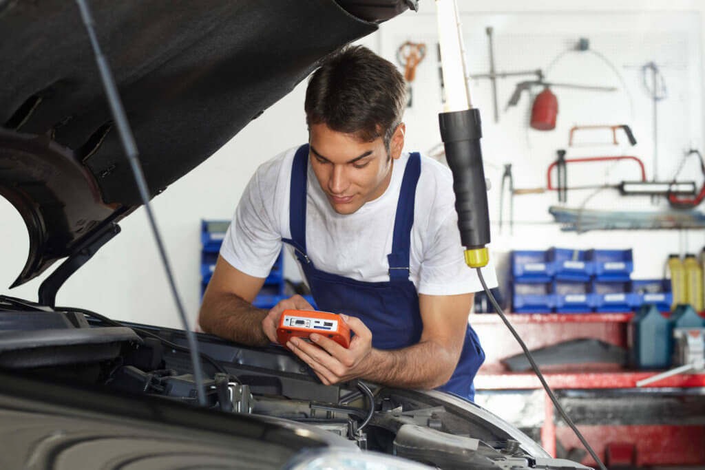 Mechanic using diagnostic tool to inspect car engine and find the problem