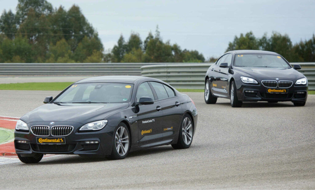 Two black BMW cars running on Continental tyres taking a corner on a race track