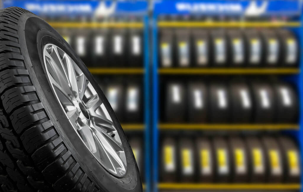 Close up of car tyre with rows of other options blurred in the background