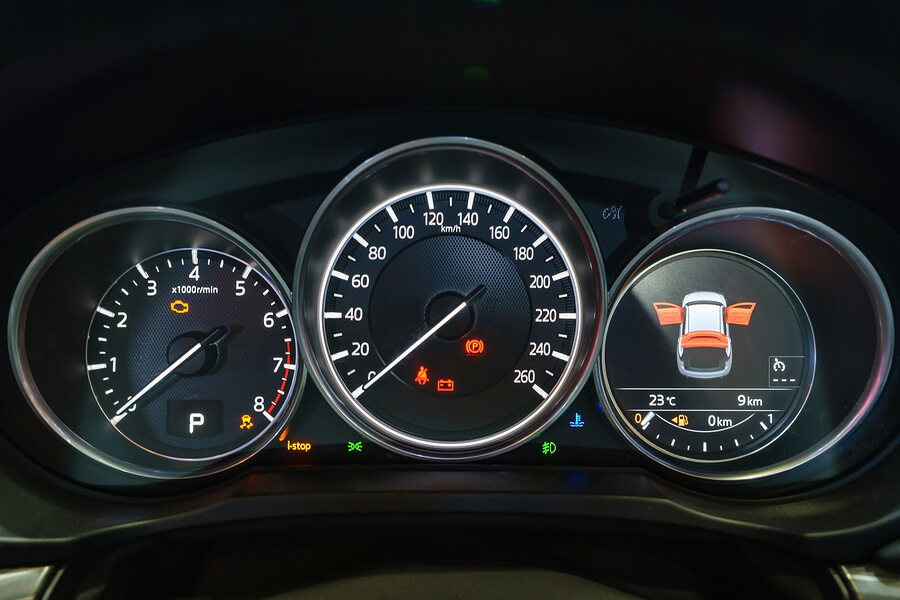 Car dashboard and speedometer with illuminated warning lights