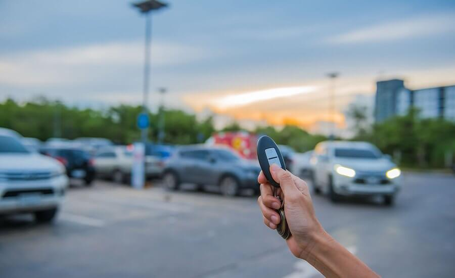 Driver holding up remote parking car key in car park at night, unfocused blurry cars in background