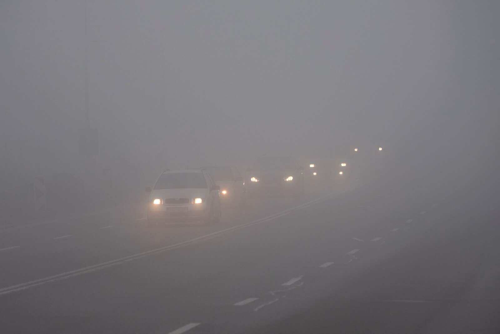 car headlights emerging out of fog. Without vehicle safety check, your lights might not work and leave you in danger!