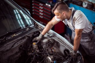 A mechanic carrying out a brake fluid change on a car's engine