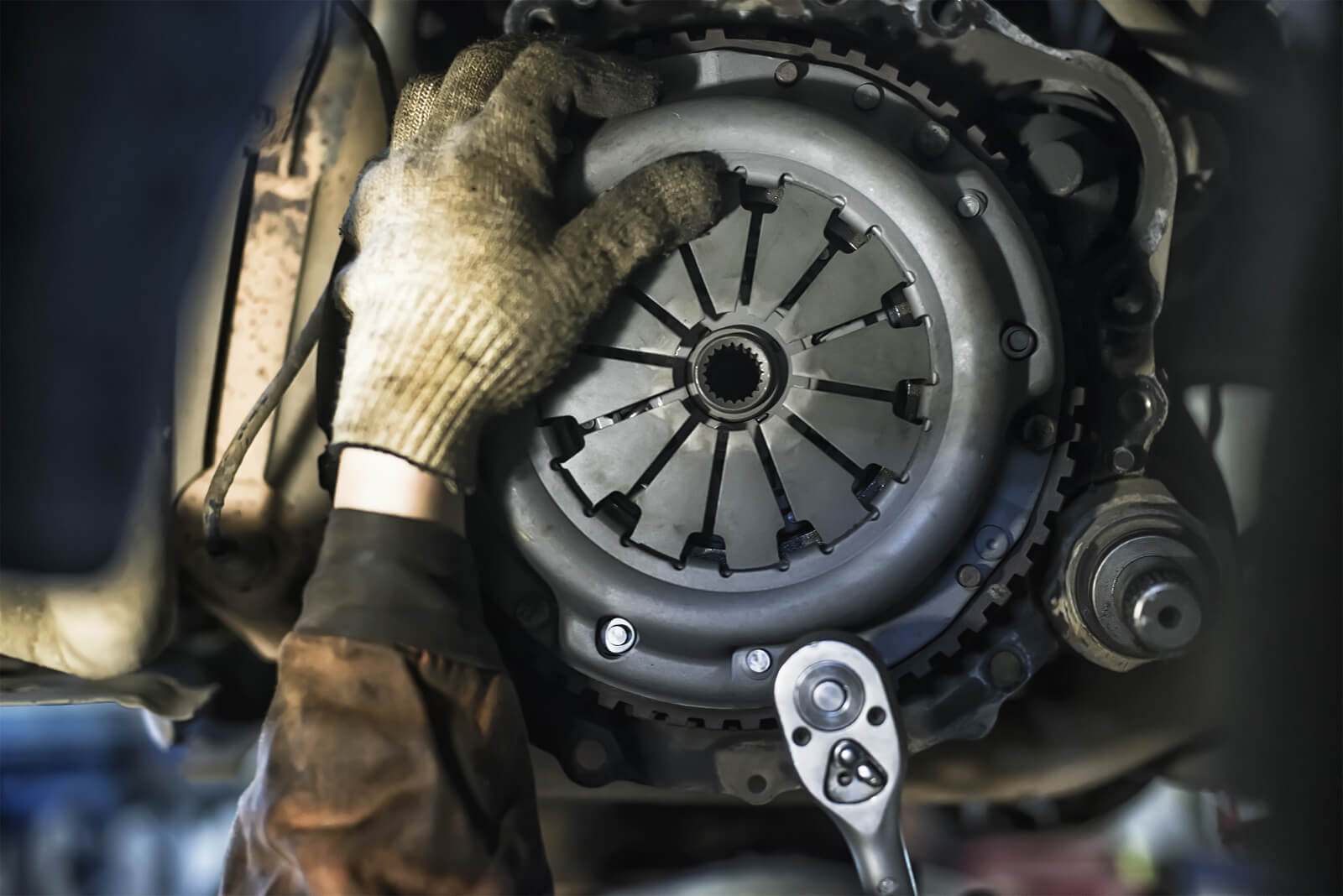 a clutch replacement in progress as a mechanic removes the assembly from the car's underside