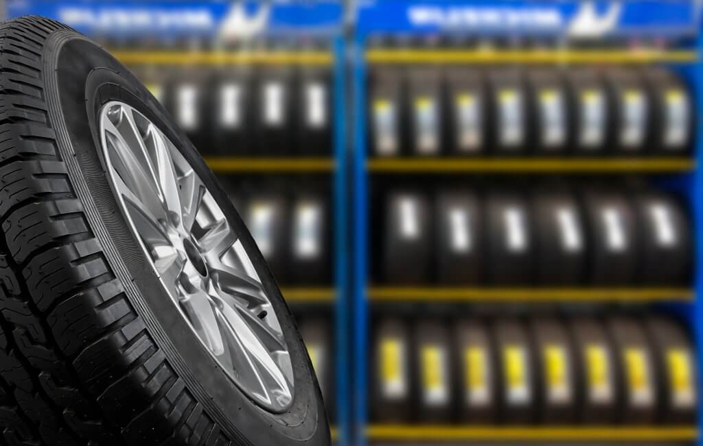 Tyre shop with prominent car tyre in foreground and blurry car tyres behind as part of a tyre check