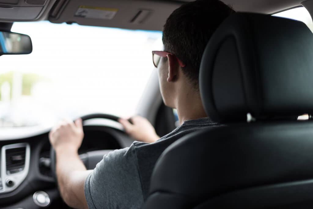man sitting in driver's seat, correct posture for a long distance drive