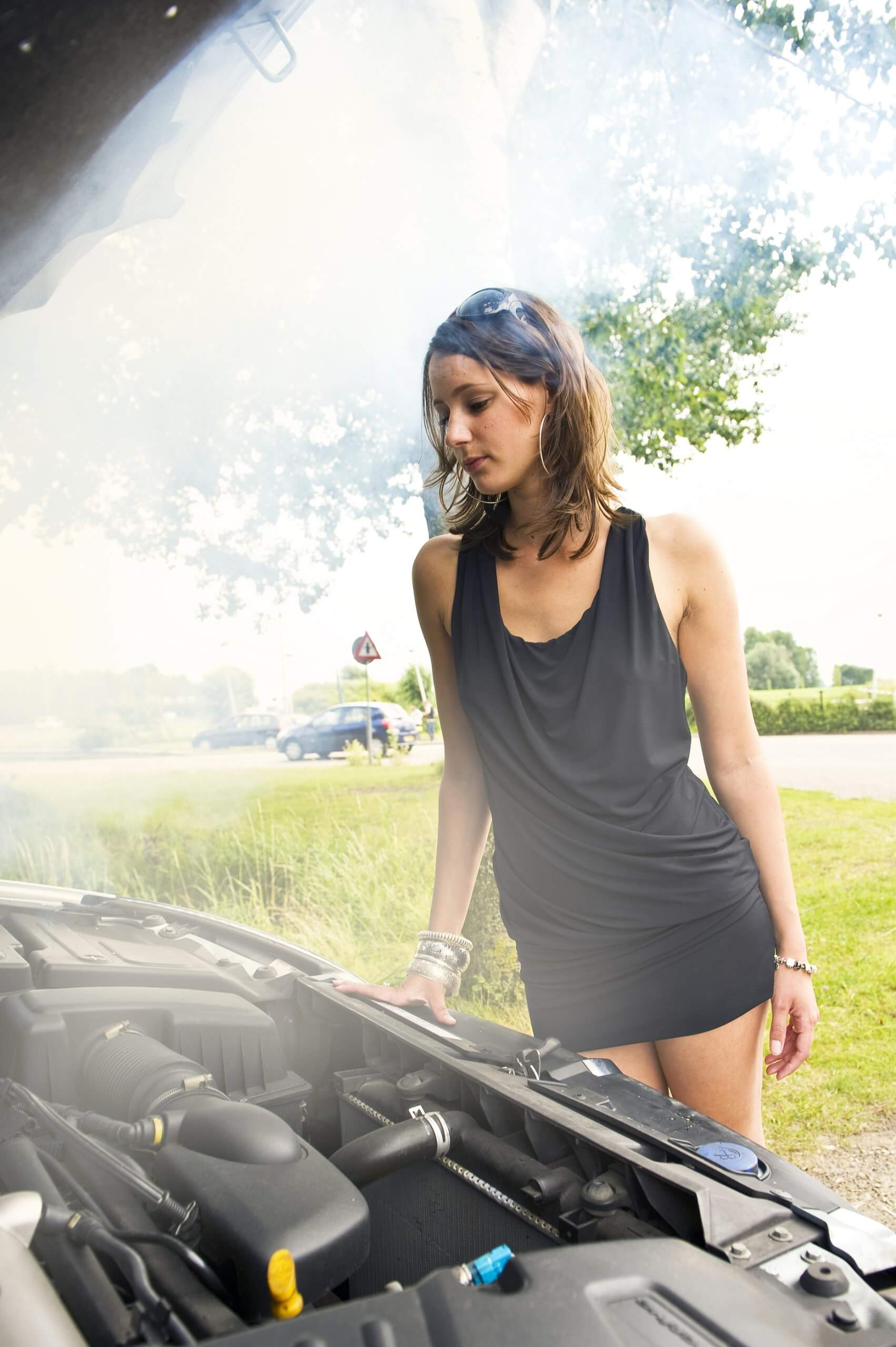 driver looking under the bonnet at smoking, overheating car engine