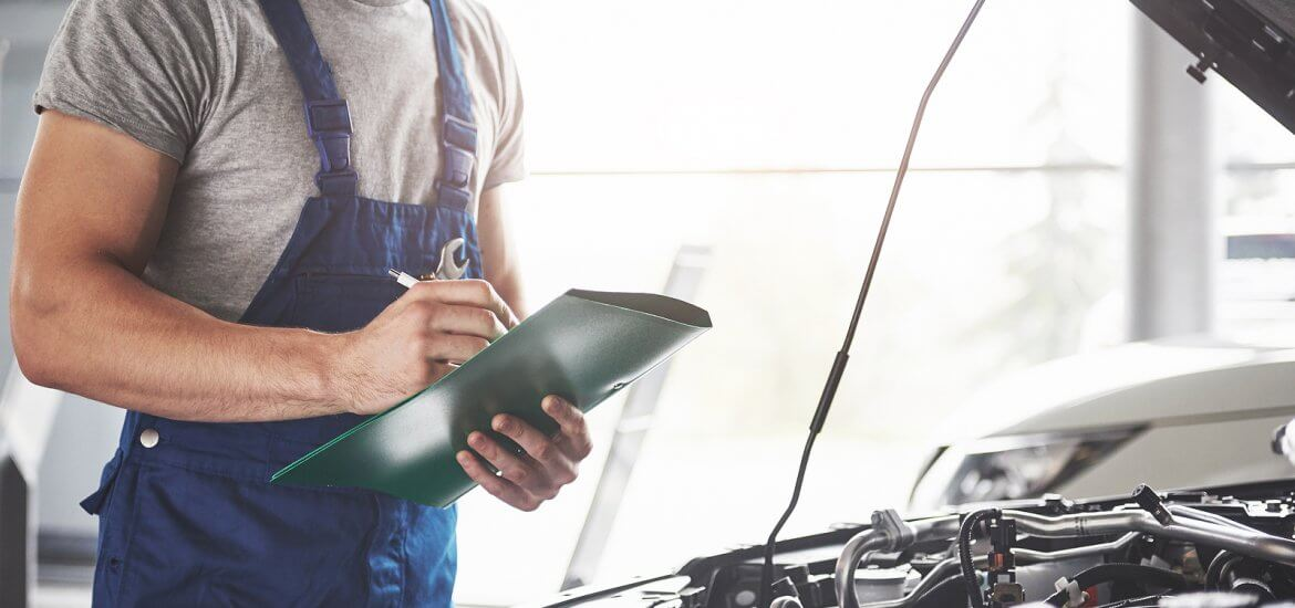 Mechanic examining clipboard during car service while inspecting the engine bay