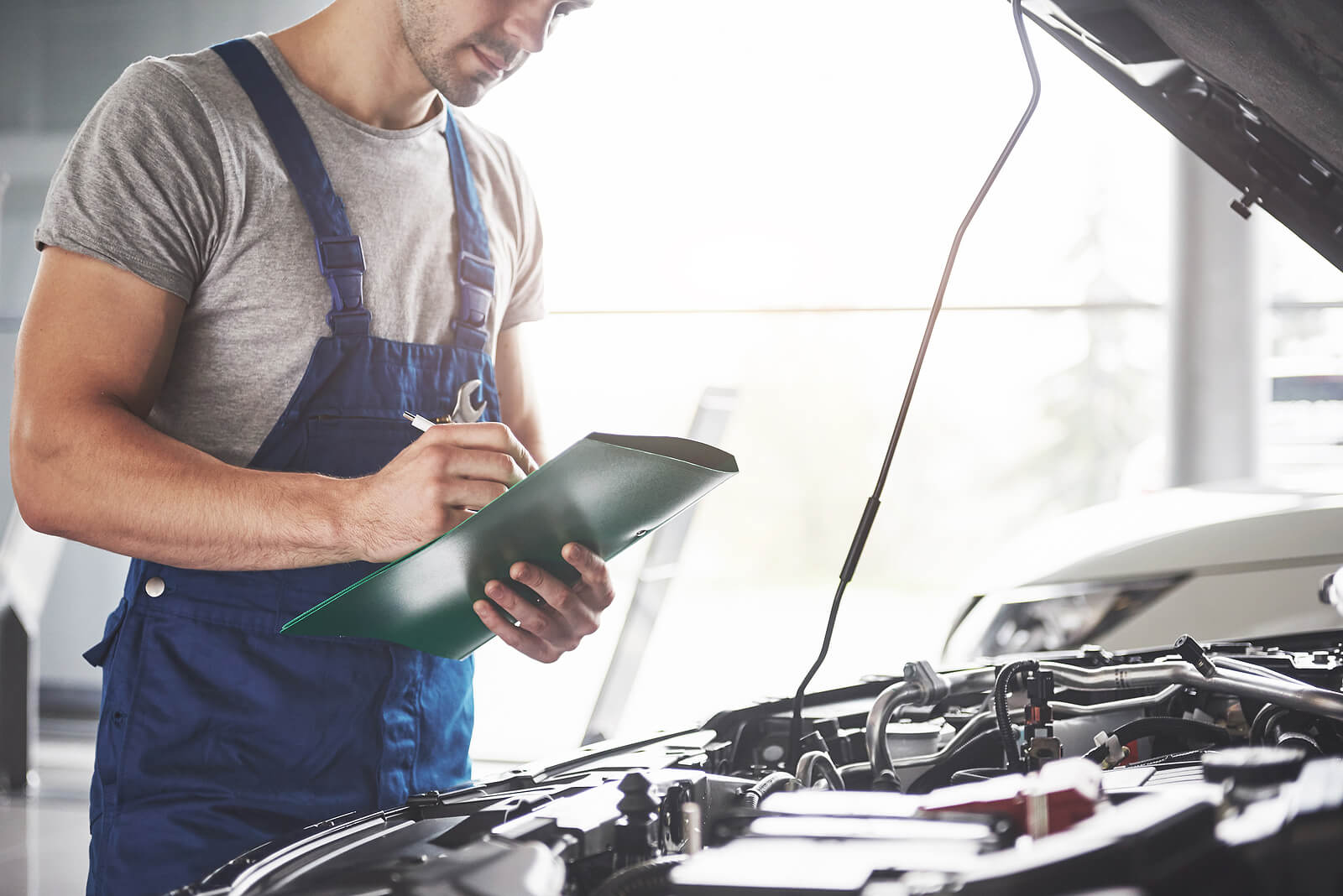 car mechanics examining clipboard with new MOT rule change included