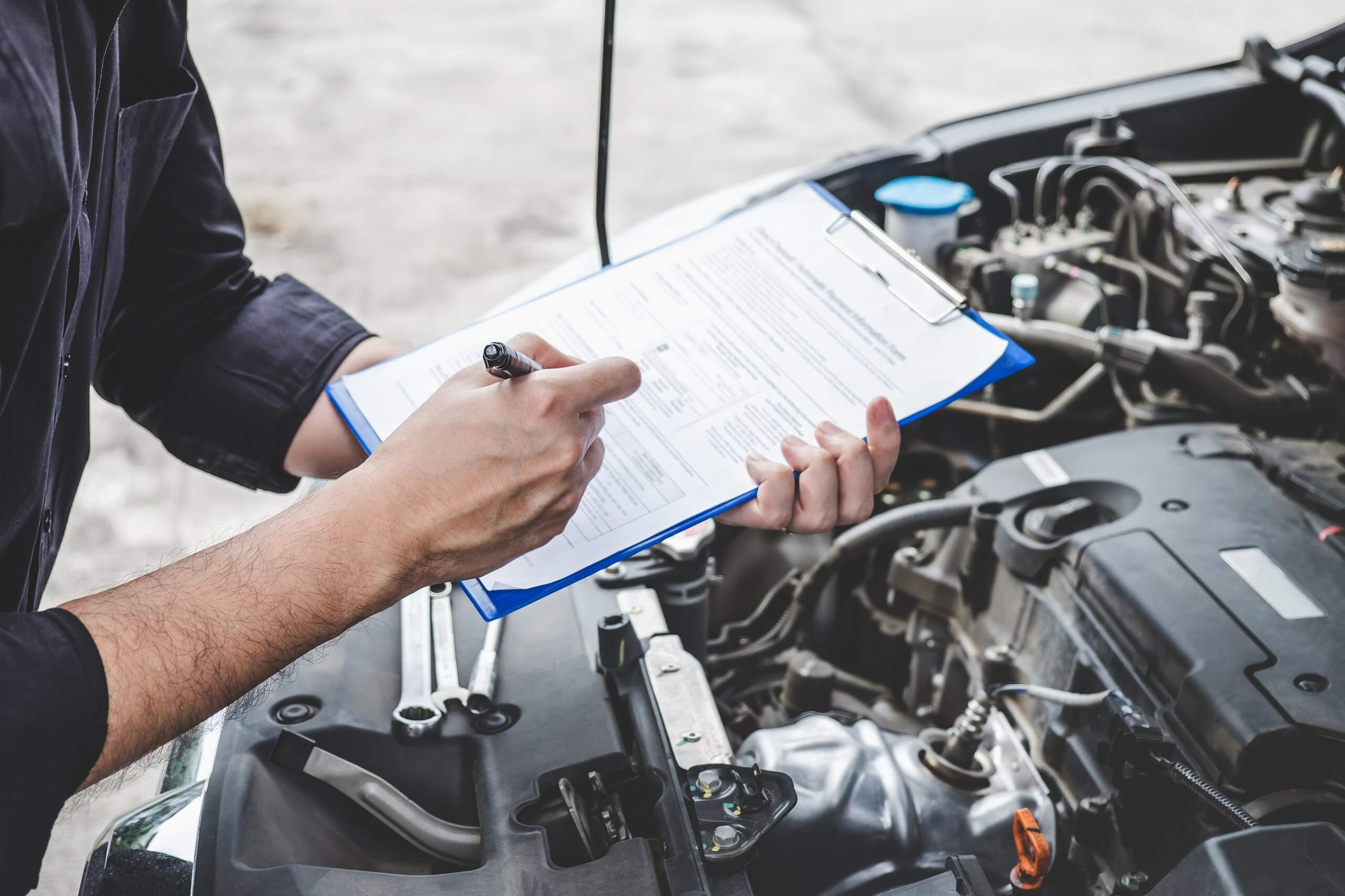 Mechanic filling out MOT certificate while inspecting car engine bay