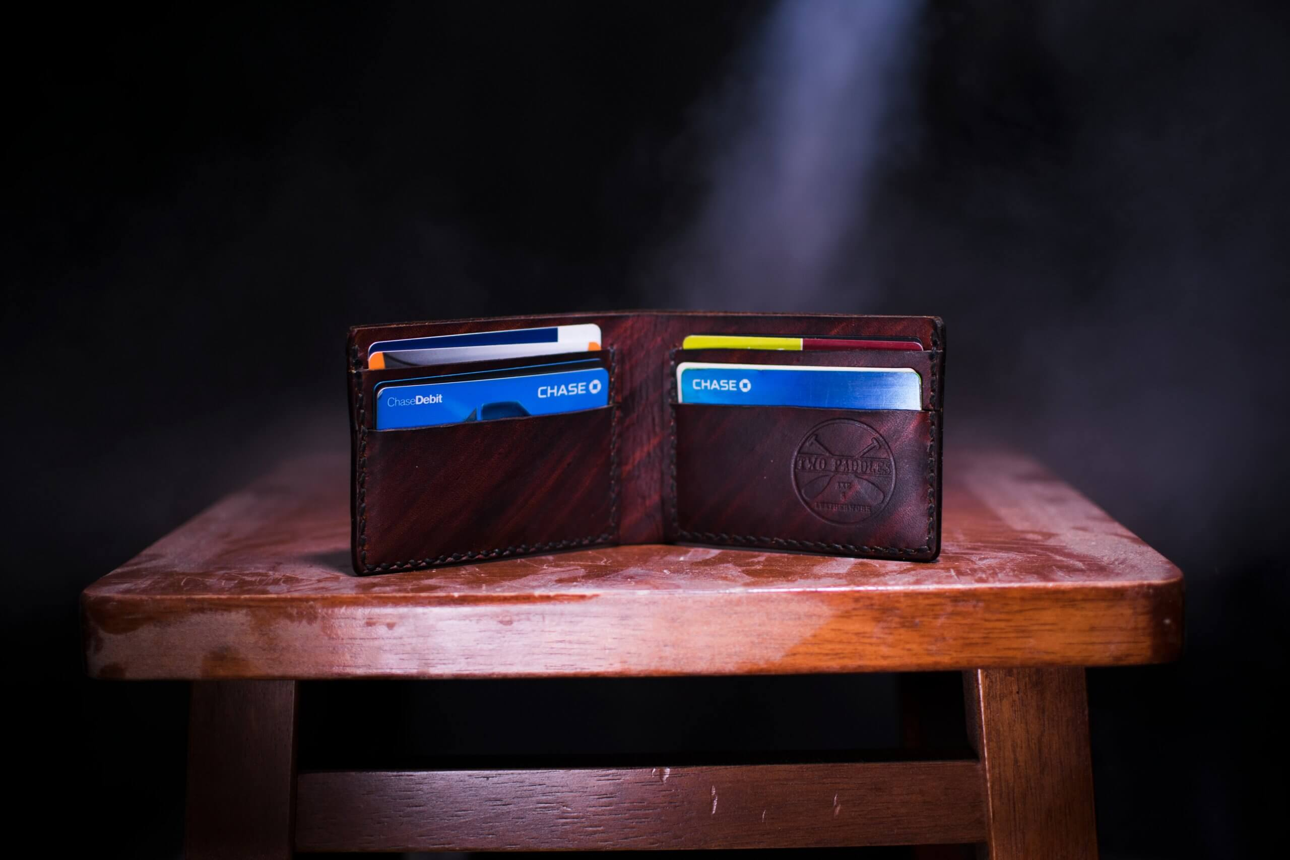 brown leather wallet on a table with credit and debit cards sticking out