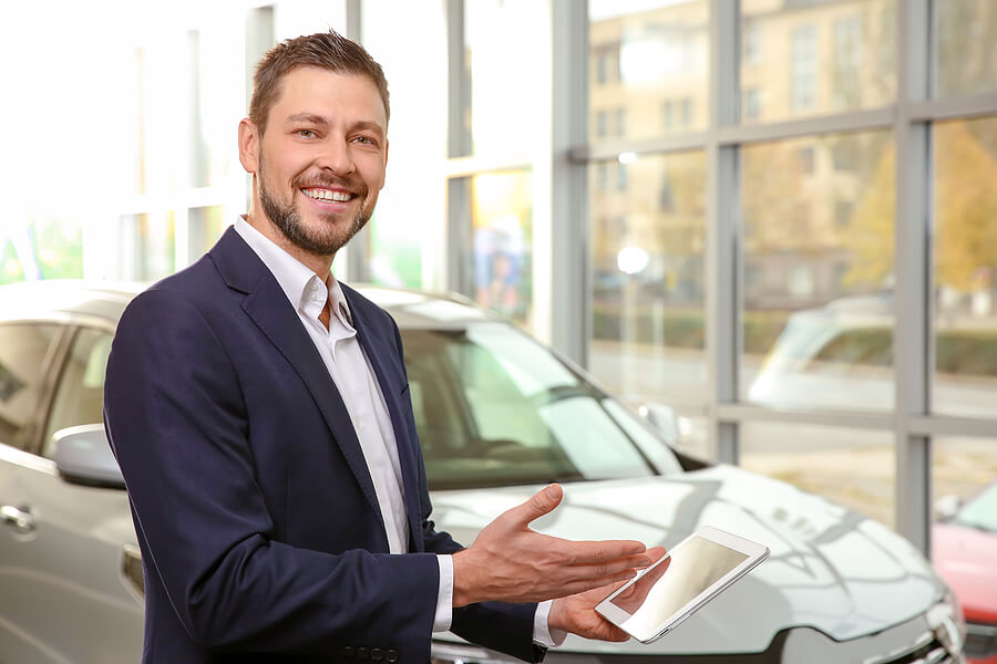 Smiling customer buying a car and pointing to his tablet device