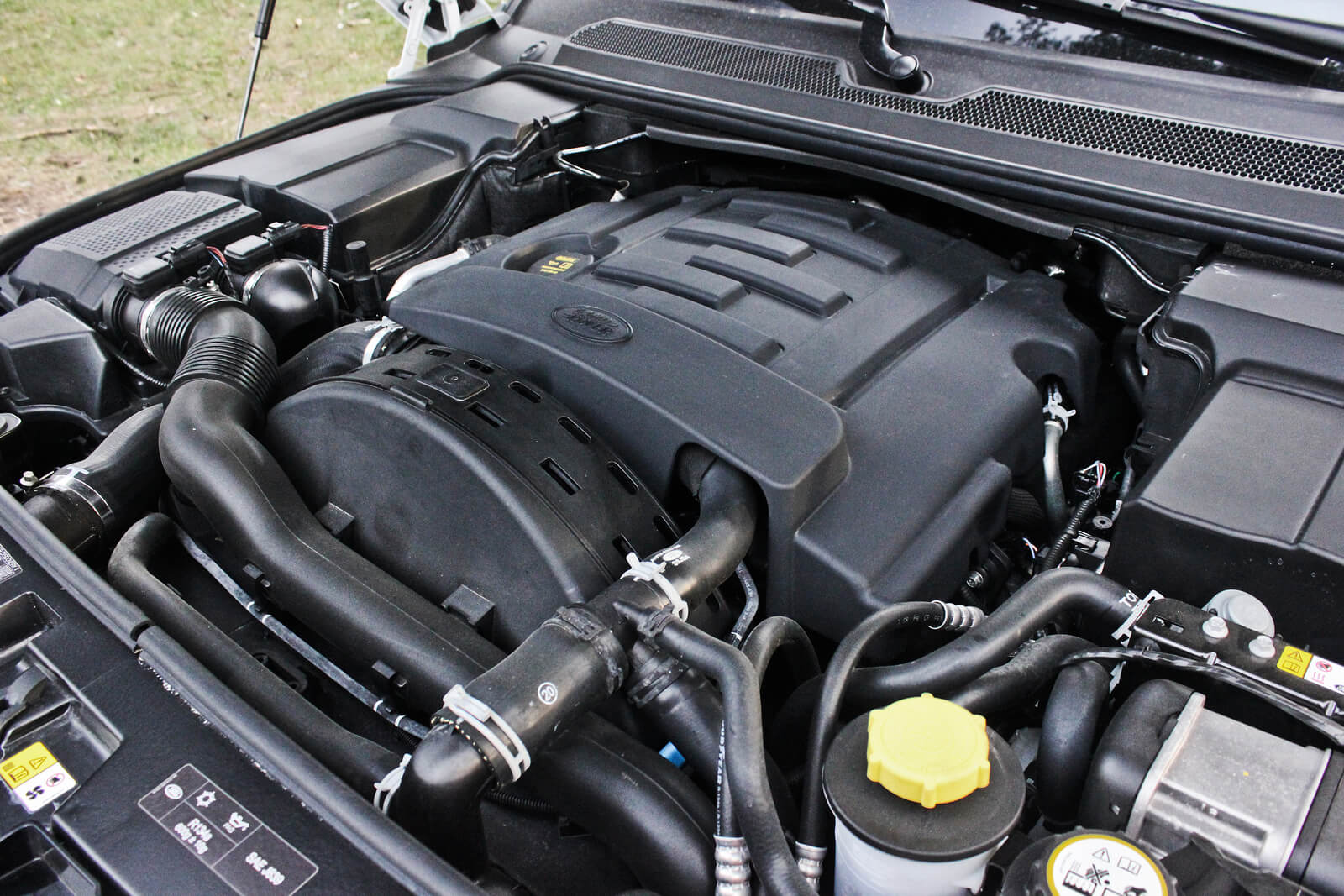Up-close shot of car engine with bonnet raised