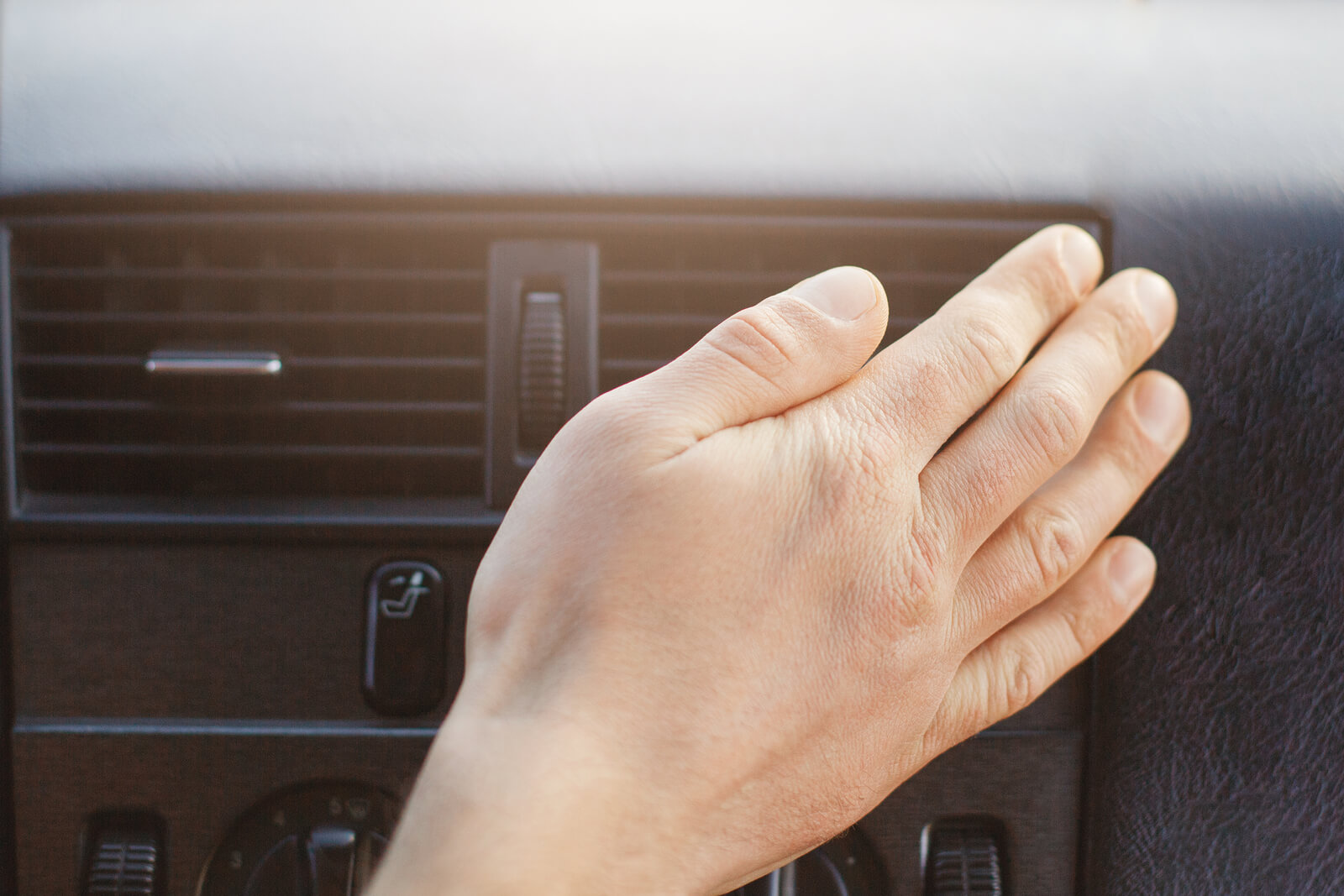 Driver's hand checking the temperature of air coming out of air conditioning unit