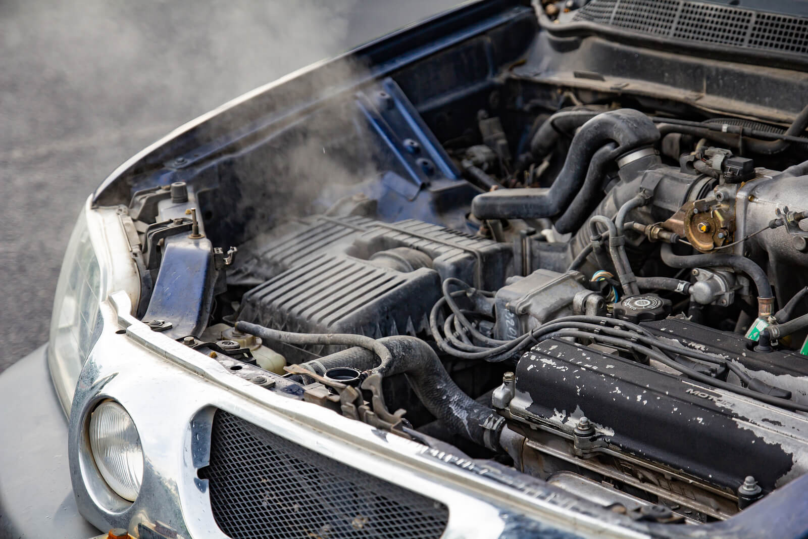 overheated car engine with lack of engine oil to lubricate moving parts