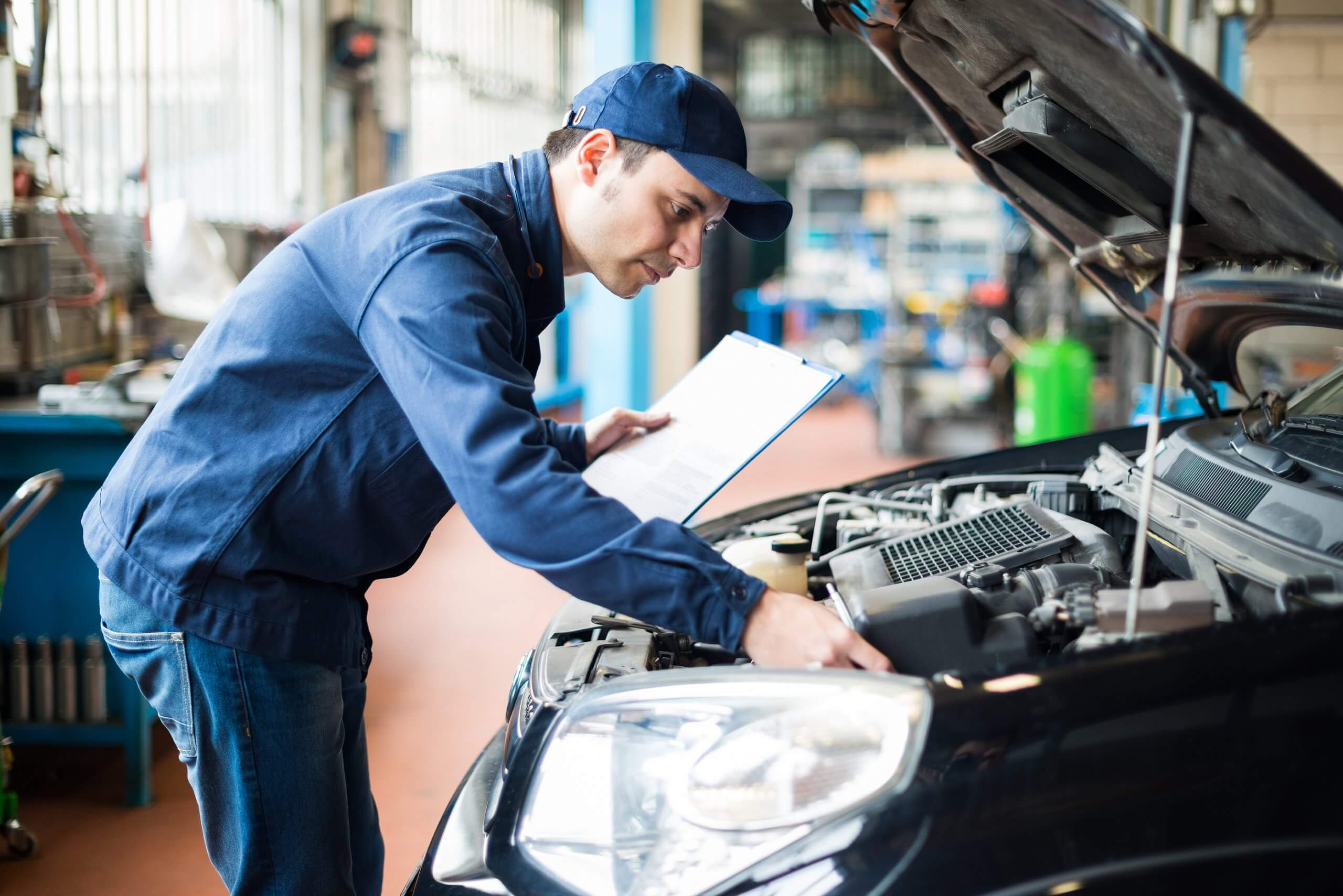 mechanic inspecting car engine with clipboard during an oil and filter change