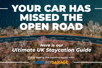 your car has missed the open road, here is our ultimate UK 'staycation', enjoy seeing the country again with BookMyGarage in white text over aerial view of road driving along oceanside with trees either side